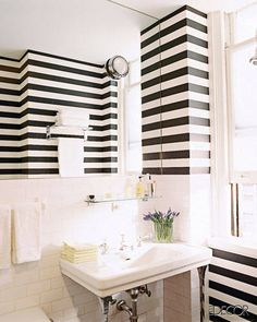 Hung horizontally, striped wallpaper brings bold panache to the guest bathroom of a minimalist Manhattan loft.