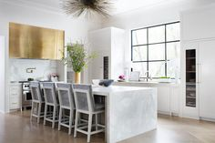 Contemporary white kitchen features four gray velvet counter stools positioned on a light wood herringbone floor in front of a marble waterfall island lit by a brass sea urchin chandelier.