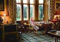 The Queen at her desk at Balmoral. In front of her is a touching photograph of her as a young girl with her father, while behind her is a cuddly toy corgi and a Bakelite telephone which has no numbers as it connects directly to the switchboard. Note the old style TV!