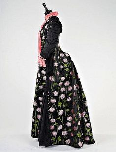 A K&M Davies of Bayswater brocaded silk evening gown, circa 1885-90, labelled to the waistband, woven with striking pink and lime hydrangeas on a black ground, tight ruched sleeves, the bodice front in-filled with rose-pink chiffon; together with an optional satin stomacher panel (which gives extra width at the front); and a lilac taffeta petticoat - side