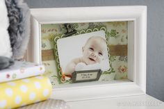 """For this baby photo display, we embellished the back of this 8"""" x 6"""" shadow box frame with scrapbook paper and jute ribbon. Then we mounted the photo on two kinds of cardstock. The lacy border was made with  a paper punch, and 3D adhesive makes the picture pop. Finishing touches: metal clip and metal nameplate!"""