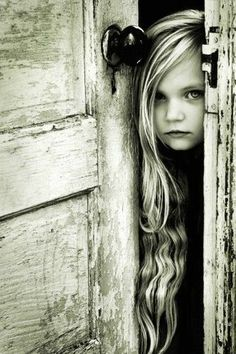 focus on girl looking through door opening, especially face & hair in black + white