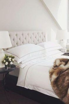 Cozy and classic bedroom with faux fur throw, crisp white bed linens, black pedestal side table, white ceramic table lamp, and tufted headboard in ivory linen.