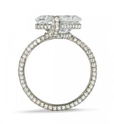 Centering an emerald-cut diamond weighing 4.06 carats, with additional pavé set diamonds. Mounted in platinum.