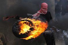 Un Palestinien met le feu à un pneu lors de violents affrontements avec l'armée israélienne (Crédit image : Jack Guez/AFP)