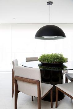 Mesa preta com tampo de vidro e cadeiras de madeira com estofado branco.