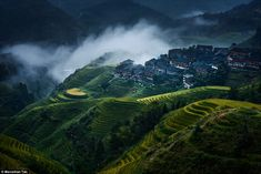 Brooding stormy skies accentuate the drama in this image of Chinese paddy fields and a village built above them.