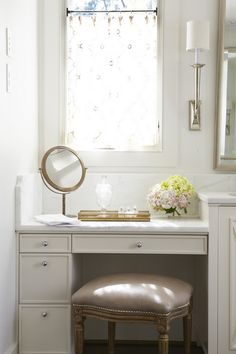 Elegant Bathroom With Silver Moroccan Pouf Tucked Under A Floating - Bathroom vanities with makeup table for bathroom decor ideas
