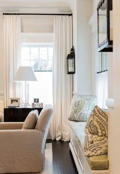 black lantern wall sconces. window upholstered seating. ivory curtains. black curtain rods. neutral colors. off white, ivory, and blue. traditional home décor ideas. café rods.: