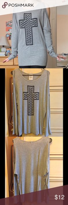 Cold-shoulder cross shirt Long-sleeve cold shoulder top with rhinestone cross design on front. Shoulders embellished with rhinestones as well. Long shirt. Very soft! Size medium. Small stain on back (pictured above) but hardly noticeable. Made by Vocal in the USA. Tops Tees - Long Sleeve