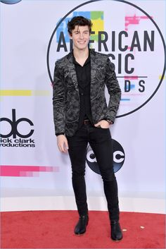 Shawn Mendes takes to the red carpet for the 2017 American Music Awards. He dons an Emporio Armani black textured vest with a black shirt and a marbled velvet blazer.