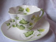 shelley tea cup, saucer, vintage 30's, made in England, fine china, yellow flowers, green leaves, scalloped shape, embossed, collectible by thevintagecalliope on Etsy