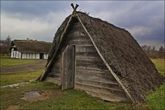 """This building contains a pit (""""grube"""" in German), possibly for grain storage. Later names for this structure might have been grubhouse, or grubhut.  It's based on the plan for a building discovered by archaeologists at New Bewick in Northumberland, although similar buildings from this period have been found all over Northern Europe.   It is thatched with heather.   Gearwe was the Anglo-Saxon name for Jarrow.  The generic name for these types of structure is Pit-House."""