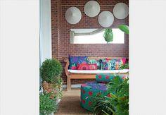 Ana Morelli, a dona deste apartamento, é designer e criou estampas bem coloridas para as almofadas de sua varanda. Elas deixam o banco de madeira mais confortável.