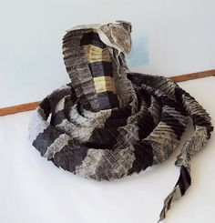 A single piece of tissue paper folded by artist Matthieu Georger to create a king cobra design