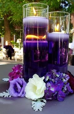 Wedding Centerpiece Ideas - Use food coloring in water with floating candles and unique inexpensive way to add wow! - I like the flowers around base of three vases-- it anchors the centerpiece and looks elegant :)