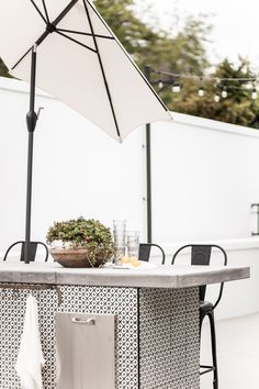 Even though its September now, the heat is still through the rough! We love having glasses out on display for our guests to use at any time when relaxing  and enjoying the outdoors! Home Exteriors | Styling and Photography by Public 311 Design | #outdoorentertainingtablescape #outdoordiningdecor #outdoortablecenterpiece #backyardentertaining #whiteoutdoorkitchen #modernfarmhouseoutdoorkitchen