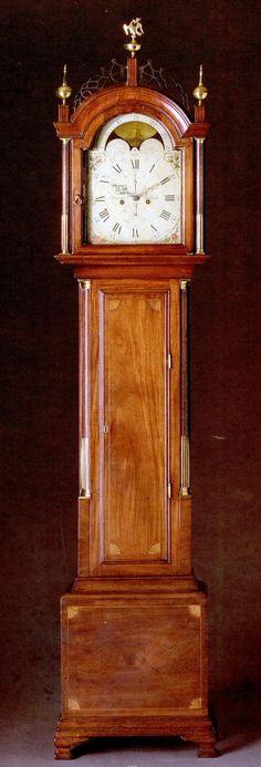 A Fine Federal Inlaid & Figured Mahogany Tall-Case Clock, Circa 1810, Signed & Labeled Simon Willard, Roxbury, Massachusetts, height 92in. by width 17 1/2in. by depth 8 3/4in. The movement of this tall case clock is signed by Simon Willard (1753-1848). Characteristic of his finest & most expensive tall-case clocks, this example has an eight-day movement with calendar & moon attachments set in an elaborate inlaid mahagony case surmounted by an eagle finial.
