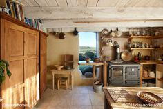 This is the interior of one of the cob homes by Adam and Katie of Clayworks [www.clay-works.com]. Their kitchen is a typical farmhouse design with a big table. It's one of the patterns recommended in the book 'A Pattern Language'. You can see more beautiful kitchens at www.naturalhomes.org/natural-kitchens.htm
