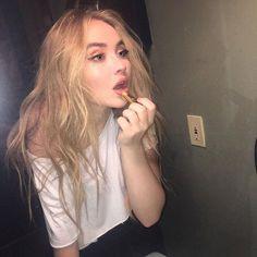 Sabrina Carpenter looking cute applying pink lipstick.
