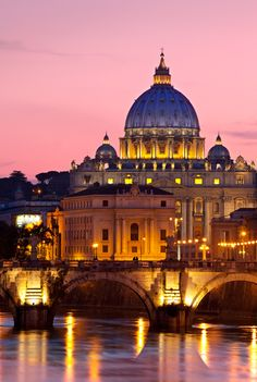 Dome of St. Peter's Basilica rises above River Tiber and Pont Sant Angelo at dusk, Rome, Italy.