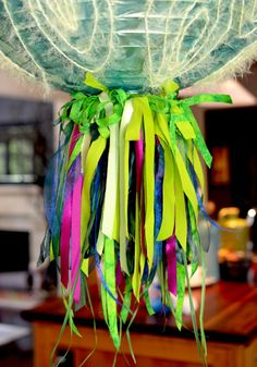 Party Lantern with fringed bottom created with locker hooking canvas and lots of Color Crazy fabric strips and ribbons. | gocolorcrazy.com