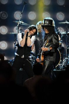 Myles Kennedy w/Slash, standing in for Axl at the Rock and Roll Hall of Fame induction performance of Guns N Roses. What I like about Myles is that he sounds a lot like Axl, but his voice is way smoother and better than Axl's voice. Plus, Myles does not try to be Axl, he just naturally sounds like Axl. However you can always tell Myles' voice from Axl's voice.
