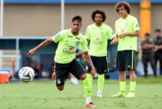 Brazilian forward Neymar (L) takes the ball observed by defenders Marcelo (C) and David Luiz during a national team training session in Serra Dourada Stadium in Goiania, Goias, on June 02, 2014. Brazil faces Panama on June 3 as preparation for the FIFA World Cup Brazil 2014 that starts on June12.
