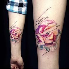 Graphic style pink rose tattoo on the left inner forearm.