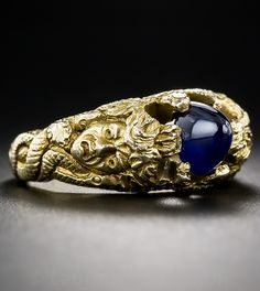 Art Nouveau Sugarloaf Sapphire Medusa Ring. The central, high-domed royal-blue sapphire, weighing approximately 2.00 carats, flanked by a matched pair of Medusa heads, with her scalar, serpentine tendrils extending all the way to create double north-south prongs. Circa 1900.
