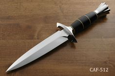 "CAF-512 : Dagger  7 7/8"" blade of 440C, mirror polish, massive 3/8"" stock, 13 3/4"" overall length, Stainless steel hilt, Black micarta handle with ivory micarta spacers, Fluted stainless steel pommel, With a padded zipper storage pouch, no sheath, Excellent condition (a few extremely fine stain spots on blade and very fine sharpening scratches near the edge. Also has some marks on the hilt.)"