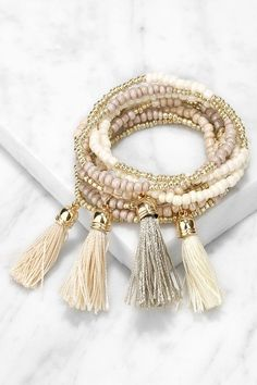 "The Talkin' Tassels Gold and Taupe Bracelet Set is sure to quickly become an outfit staple! Nine bracelets boast an assortment of taupe, ivory, and gold beads, plus tassel accents with hidden elastic threading. Bracelets are 3.5"" (relaxed) and can be worn together, or on their own!"