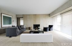 Living room house in Belgium designed by architect Vincent Van Duysen, the armchair and ottoman are by Huyghe Decoratie, the cocktail table and bench are by Christian Liaigre, the wood cabinetry is custom made, and the window blinds are by Brustor.- ELLEDecor.com