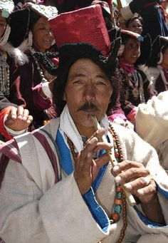 Portrait of traditional dress Ladakhi man with hat looking at camera and playing flute during Ladakh festival, Leh Ladakh India.