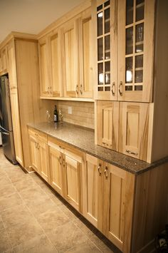 Wood-Mode /Natural Maple Cabinets- these are stock from Home Depot I think. I like the glass inserts, and what looks like either a coffee-bar/beverage bar-hide-away? or an appliance hider-of some sorts. I would want a dedicated cabinet, one for the electronics-chargers, ets. also.