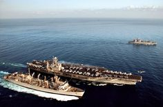 Fast combat support ship USNS Arctic (bottom) sails with aircraft carrier USS Harry S. Truman in the Mediterranean Sea. Ammunition ship USNS Mount Baker accompanies them during a simultaneous replenishment. An F-14 Tomcat launches from Truman.