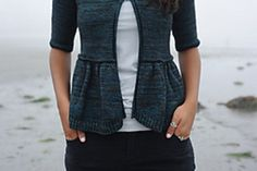 A top-down cardigan with a well-placed pleat that flatters the waist. Short row shaping at the hem gives creates a slight curve, mimicking the shape of a shore line. With elbow-length sleeves, this a cardigan for all seasons!