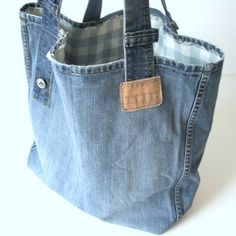 Unique handmade jeans bag made of old recycled medium blue jeans with lots of original details. Distressed pockets are stiched in front of tote, this gives the bag a very vintage look! This bag is perfect for a day at the beach or shopping in the city! Also very easy to put in your suitcase for summer holiday or city trip! The bag is made of an old jeans with original details like: old pockets, signs and leather labels. there is a big zippered pocket inside for smaller things. Size: 19,6…