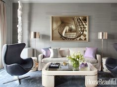 """Gray walls covered in Kneedler-Fauchère's Fine Hemp give the living room a """"sexy nighttime coziness and sophistication,"""" Dhong says. Lavender silk pillows add a jolt of iridescent color, and the viscose rug from Stark """"shimmers like a pool of water."""" Gleaming polished nickel Porter lamps from Robert Abbey"""