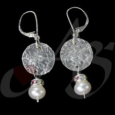 This piece is a pair of earrings. These earrings are made with sterling silver, crystals and pearl. The sterling silver was hand cut and hand stamped. The roundel of crystals is a series of 8 set Chinese crystals. On the bottom are white sheen freshwater pearls.