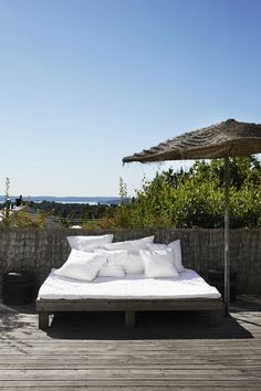 Home-built bed on the terrace in the shadow under the parasol. The bamboo fence patronises beautifully over the years and becomes silver gray, which gives an exotic feature.