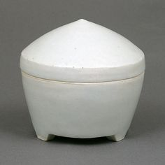 Bernard Leach  |   Lidded Cogo (ca.1965): Porcelain, Y'ing Ching celadon glaze, on carved tripod foot with domed conical lid, impressed BL & Leach Pottery seals (h8.2, d8.7cm)