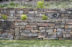 The size, color, and shape of the material used for a retaining wall should be well considered.  How it's stacked is just as important.  Even when all of these have been considered, having a planting space below it would have softened it even more.