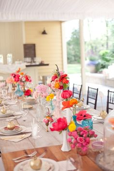 bright coloured flowers in bud vases/ wine bottles and other available small containers (mismatched!)