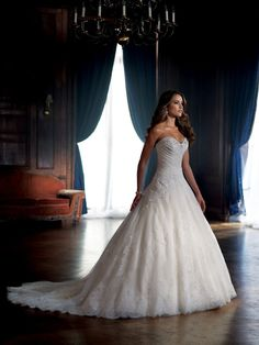 This tulle ballgown has a flattering sweetheart neckline with an asymmetrical bodice. The lace and crystal embellishment decorates the bodice as it flows into a tulle shirt with lace applique. A corse