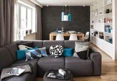 salon contemporain avec canapé rembourré en gris foncé,coussins décoratifs et bibliothèque