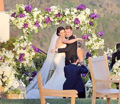 Nick Carter and Lauren Kitt are posted under an elaborate floral archway, created with hydrangea, orchids, and roses.