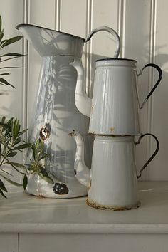 white enamel pitchers. We had a LOT of emanel ware on the farm.  Don't know how country people made it without these staples.                   ****