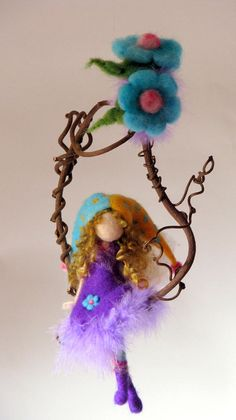 Needle felted fairy sitting on a kiwi twig. Waldorf inspired – without details of her face. Each fairy is original. Size: fairy sitting: the widest place of the twig: the circle of the twig diameter. Thank you for visiting my shop. Fairy doll Needle felted Waldorf inspired Magic fairy