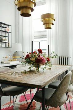 table en bois clair, chaises beiges dans la salle à manger chic, tapis beige, orange, rouge
